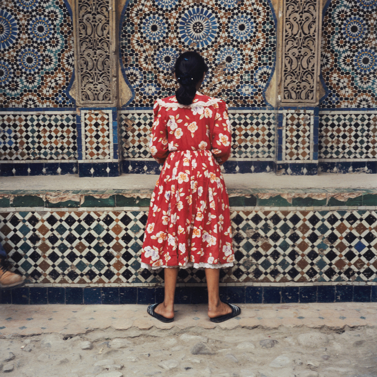 A color photo of a woman facing a wall with Islamic style tile work. She is wearing a red and white floral patterned dress.